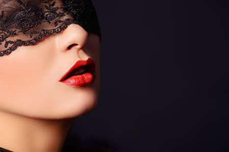 Close-up portrait of a charming  woman in black lace mask. photo