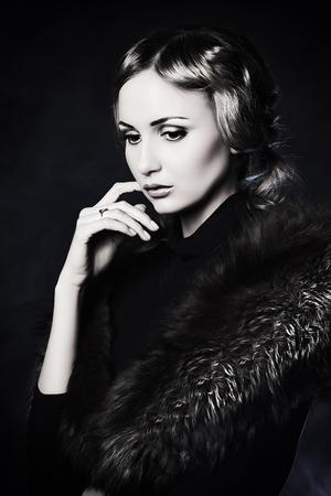 silver fox: Mujer joven elegante en ropa negra que presenta en el estudio. Foto de archivo