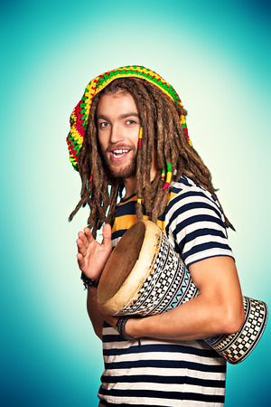 Portrait of a rastafarian guy playing his drum. photo