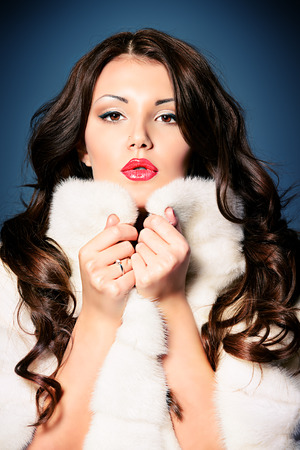 Fashion shot of a beautiful young woman in white fur coat. photo
