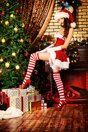 Sexual young woman in Santa Claus costume posing in Christmas decorations. Stock Photo - 24927341