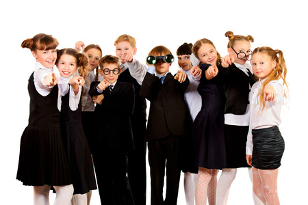 Group of cheerful schoolchildren standing together. Isolated over white. photo