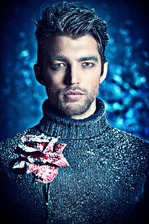 Portrait of a handsome man dressed in winter clothes, holding a rose, covered with snow. photo