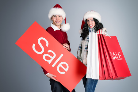 Happy young couple standing with a lot of shopping bags. Sale.  photo