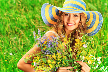 Portrait of a romantic smiling young woman with a bouquet of wild flowers outdoors. photo