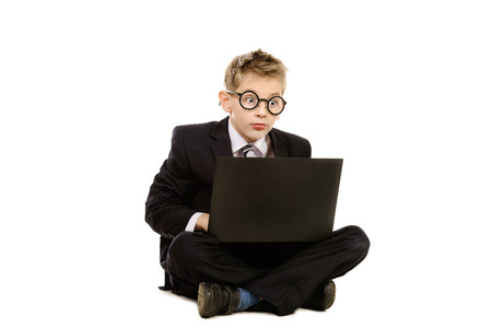 kids laptop: Portrait of a boy in a suit and glasses sitting with his laptop. Isolated over white.