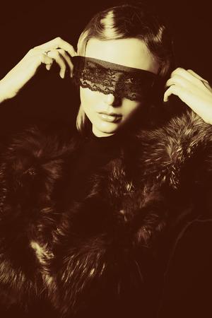 silver fox: Mujer joven elegante en ropa de color negro y encaje negro m�scara posando en el estudio.
