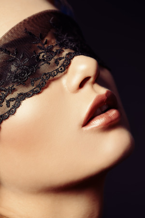Close-up portrait of a charming  woman in black lace mask. Stock Photo - 25060132