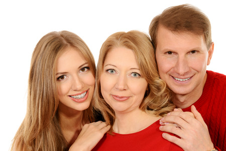 Happy elderly parents standing with their adult daughter. Isolated over white. photo