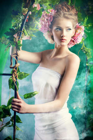 Beautiful young woman standing under an arch of flowers and overgrown loach. Magic of the spring. photo