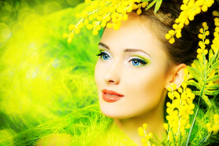 Portrait of a beautiful girl with mimosa flowers. Spring. photo