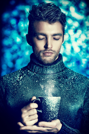 Portrait of a handsome man dressed in winter clothes, covered with frost, drinking hot tea.