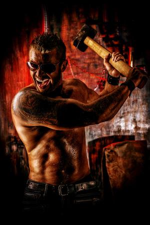 violence in the workplace: Hombre muscular hermoso con martillo de trabajo en el antiguo garaje.