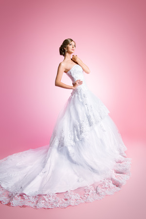 Full length portrait of a beautiful charming bride in a luxurious dress. Over pink background. photo