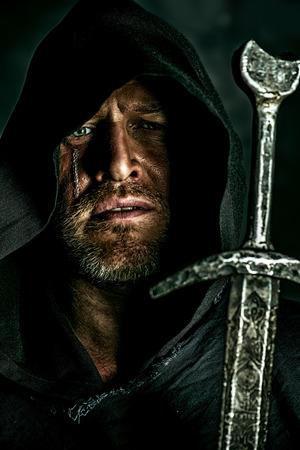 Portrait of a courageous warrior wanderer in a black cloak and sword in hand photo