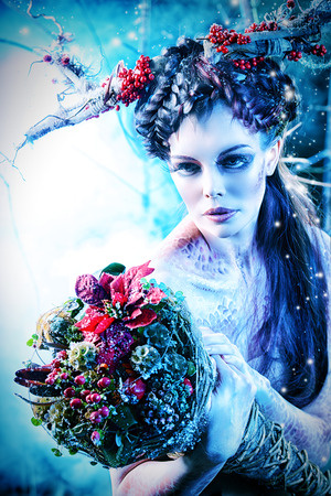 body paint: Art project. Close-up portrait of a beautiful girl in the image of a wood nymph holds winter bouquet.