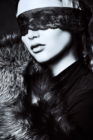 silver fox: Elegant young woman in black clothes and black lace mask posing at studio.