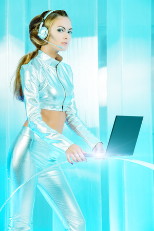 latex woman: Beautiful young woman in silver latex costume with futuristic hairstyle and make-up working on a laptop. Sci-fi style.