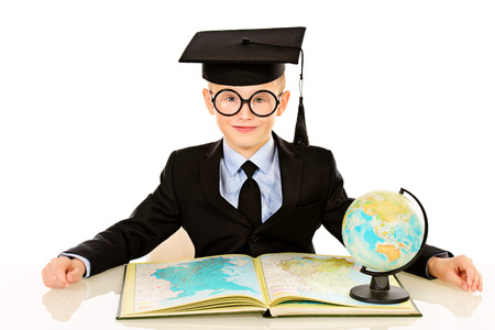 Serious schoolboy in academic hat sitting at the table with a book and globe. Isolated over white. photo