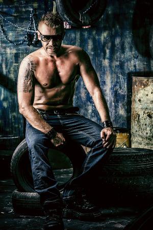 violence in the workplace: Hombre muscular hermoso en el antiguo garaje.