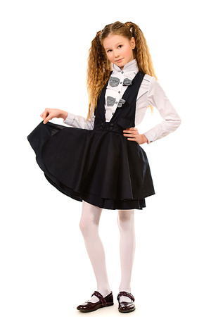 Portrait of a ten years schoolgirl wearing uniform. Isolated over white. photo