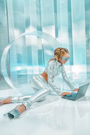 Beautiful young woman in silver latex costume with futuristic hairstyle and make-up working on a laptop. Sci-fi style. photo