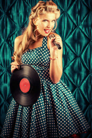 Pretty pin-up woman singing with vinyl record over vintage background. photo