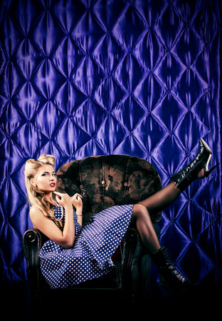 Charming pin-up woman with retro hairstyle and make-up sitting in the armchair over vintage background. photo