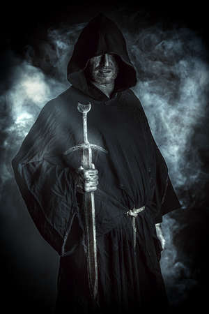 Portrait of a courageous warrior wanderer in a black cloak and sword in hand