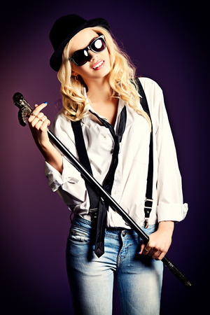 Elegant blonde woman wearing white shirt and black hat and tie. Over dark. photo