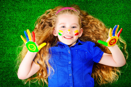 Laughing little girl painted in bright colors lying on green grass  Happy childhood  photo