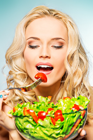 Portrait of a beautiful young woman eating vegetable salad. photo