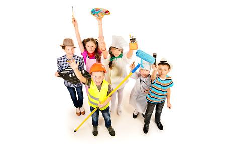 Un grupo de niños vestidos con trajes de diferentes profesiones. Aislado en blanco. Foto de archivo