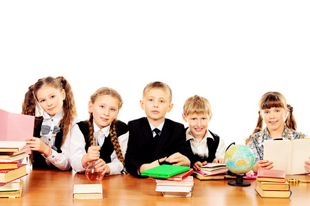 Schoolchildren sitting together at the table and engaged in lessons. Isolated over white. photo
