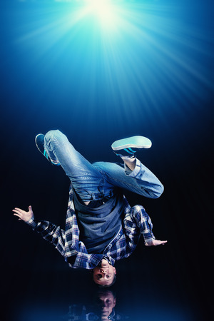 Modern young man dancer over black background. Stock Photo