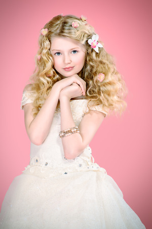 belle: Portrait of a girl with beautiful gentle appearance in white festive dress. Over pink background. Stock Photo