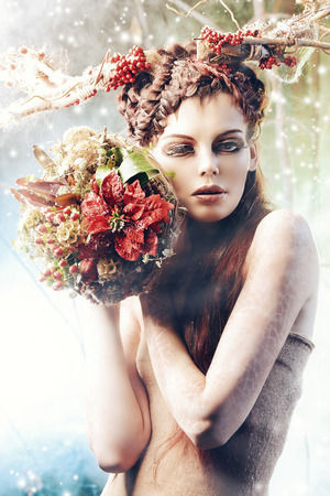Art project. Close-up portrait of a beautiful girl in the image of a wood nymph holds winter bouquet. photo