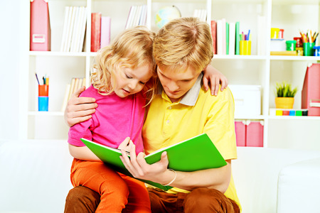 play room: Elder brother and his little sister sitting together on sofa at home and reading a book.
