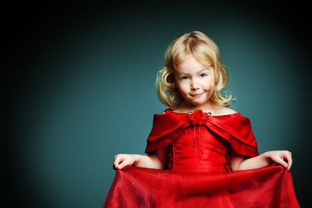 Portrait of a smiling little angelic girl in a beautiful red dress. photo