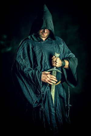 reenactment: Portrait of a courageous warrior wanderer in a black cloak and sword in hand. Historical fantasy.