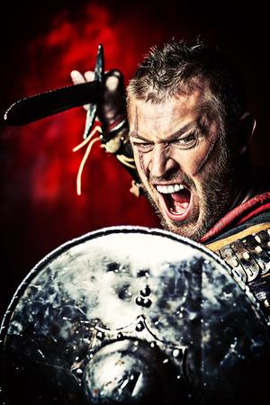 romano: Retrato de un antiguo guerrero valiente en armadura con la espada y el escudo. Foto de archivo
