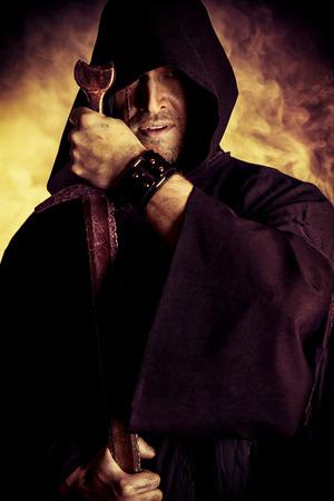 espadas medievales: Retrato de un guerrero valiente trotamundos en un manto negro y una espada en la mano. Fantas�a hist�rica. Foto de archivo