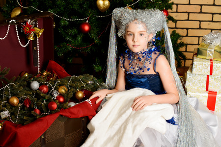 Portrait of a beautiful girl who looks like a little snow Queen. Christmas background. photo
