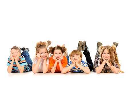 Happy children lying on a floor and smiling at camera. Isolated over white. photo