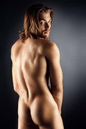 Hombre desnudo musculoso sexual que presenta sobre fondo oscuro.