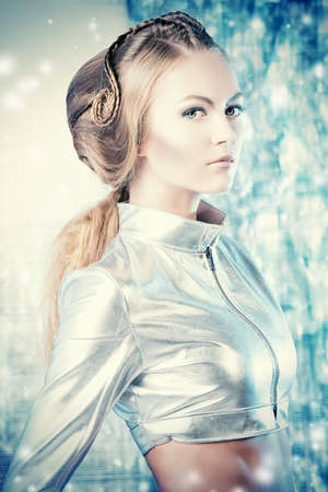 Close-up portrait of a beautiful young woman in silver latex costume with futuristic hairstyle and make-up. Sci-fi style. photo