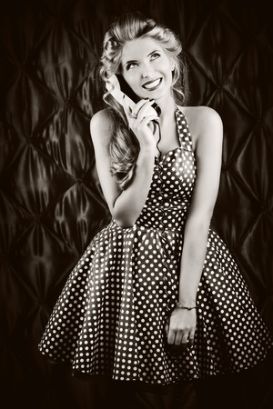 Charming pin-up woman with retro hairstyle and make-up talking on the phone. photo