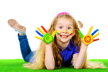 child finger: Laughing little girl painted in bright colors lying on green grass. Happy childhood. Stock Photo