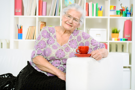 Smiling senior woman sitting at home on a sofa and drinking tea  photo