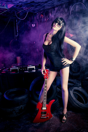 Beautiful sexual girl playing electric guitar in the old garage.